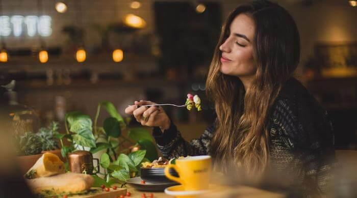 unsplash: woman happily enjoying dinner pasta