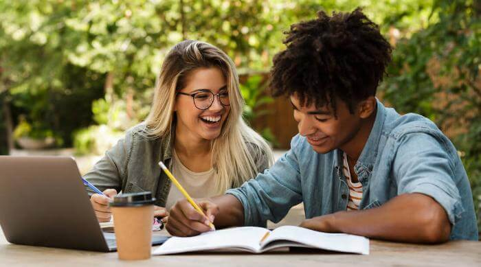 Shutterstock: Cheerful young multiethnic couple spending time together at the park, studying while sitting at the table with laptop