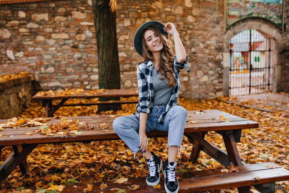 A young woman smiles while sitting on a picnic table surrounded by autumn leaves