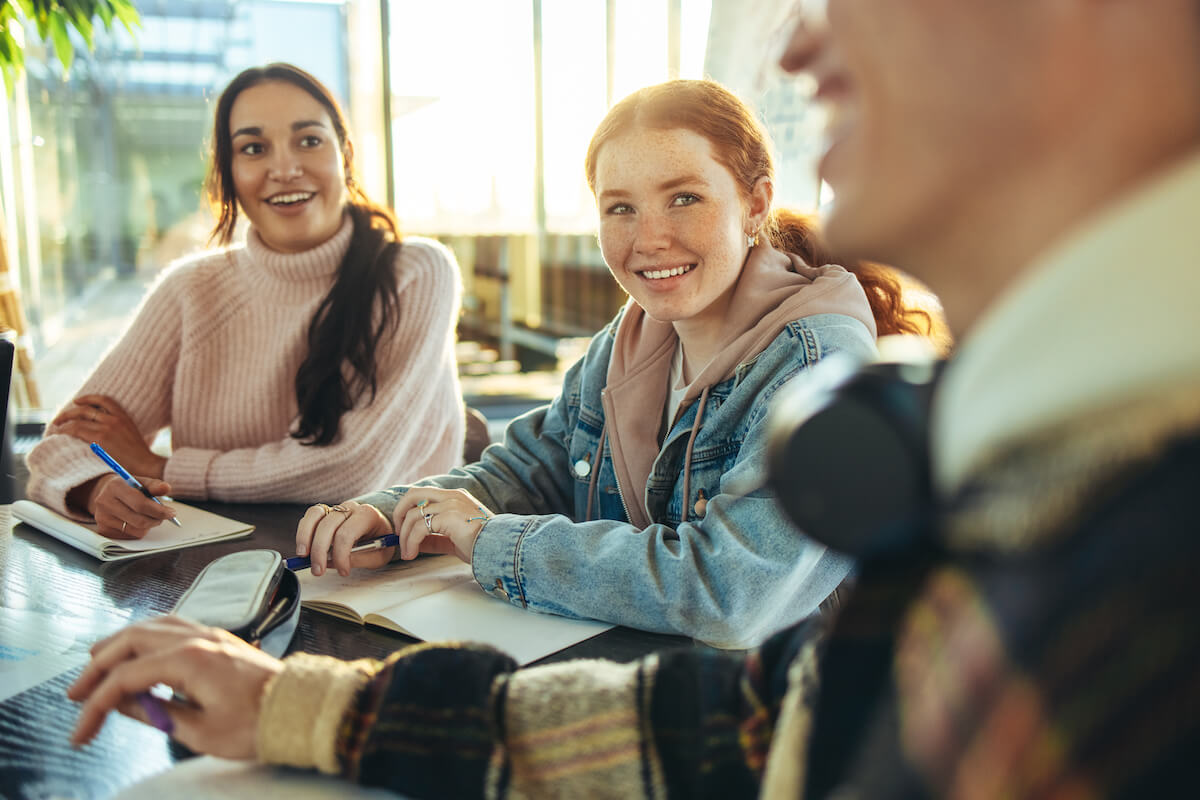 Shutterstock: Cheerful group of students in a discussion in high school. Young people smiling while studying in college campus.