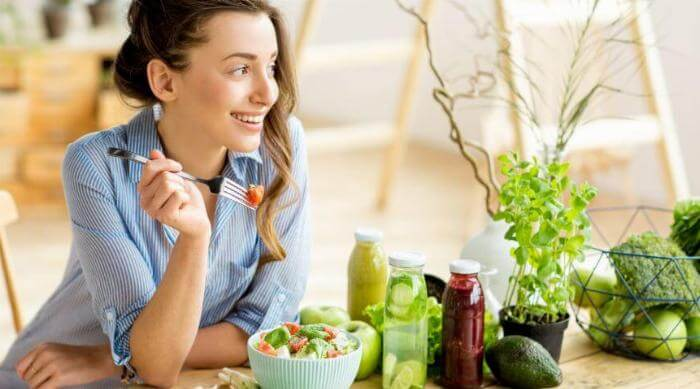 A young girl smiles while eating a healthy salad