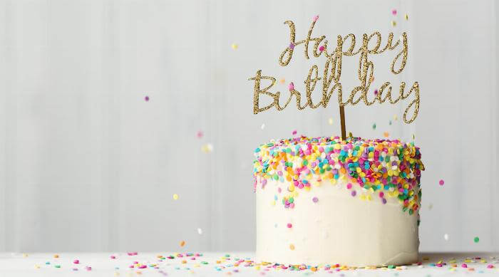 Shutterstock: Colorful birthday cake with golden happy birthday banner and falling sprinkles