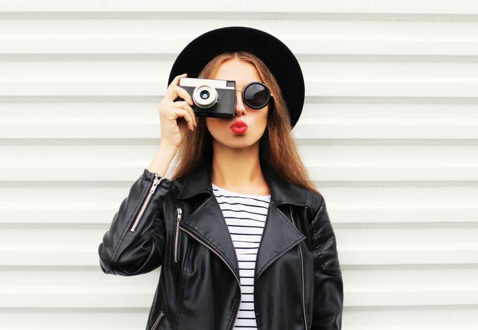 A young girl wearing a hat and leather jacket holds a camera over her face