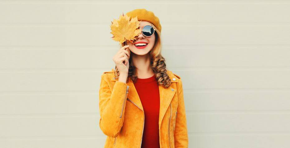 A young girl wearing fall clothing smiles and holds a leaf over her face