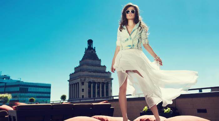 Shutterstock: Beautiful woman white loose skirt, high heels, and jeans jacket standing on the bed on the rooftop