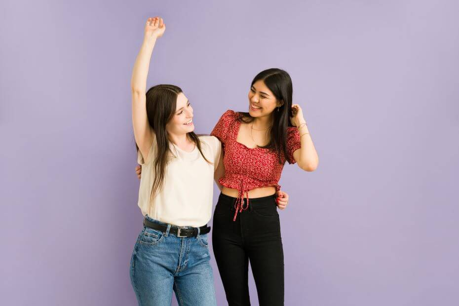 two friends stand and smile at each other in front of a purple wall