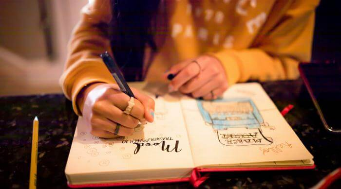 Shutterstock: Closeup of young teen girl writing in bullet journal on mood tracker page