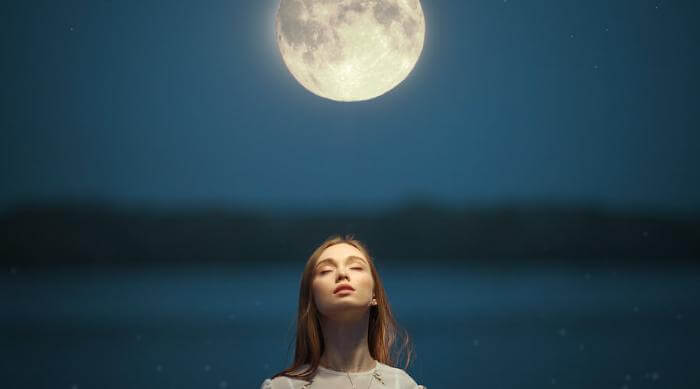 Shutterstock: Woman looking up at full moon