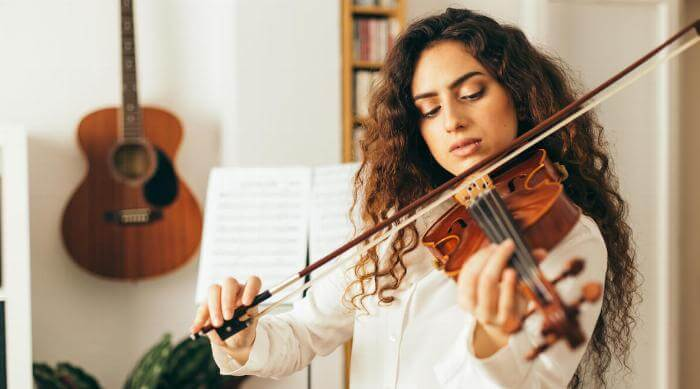 Shutterstock: Girl playing violin. Young woman studying music alone at home in the living room with natural and soft light. Curly long and brunette hair, elegant dressed.