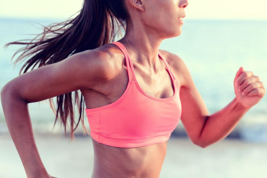A young woman running in a pink sports bra