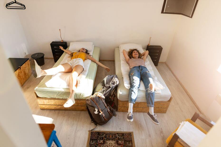 Two college roommates relax on their new dorm beds