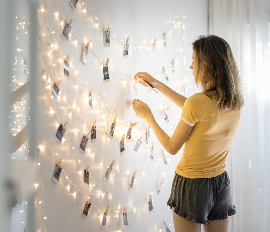 A college student decorates her dorm with hanging lights and photos