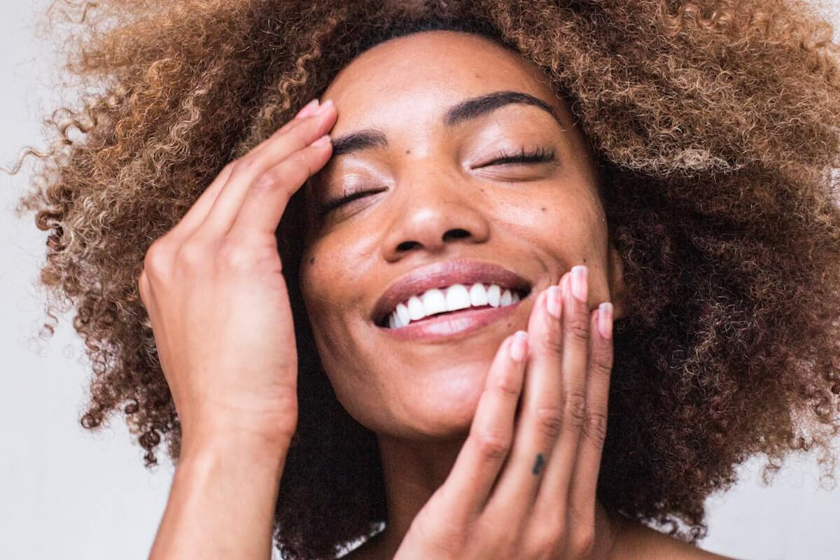 Unsplash: Woman with fresh skin looking happy smiling touching face
