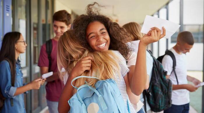 Shutterstock: Two girls celebrating exam results in school corridor