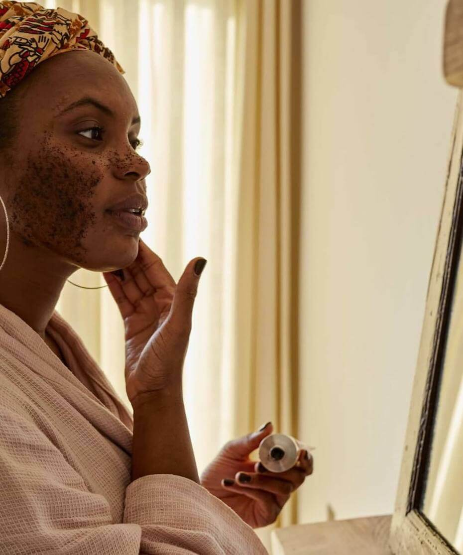 UpCircle woman applying coffee exfoliant to face